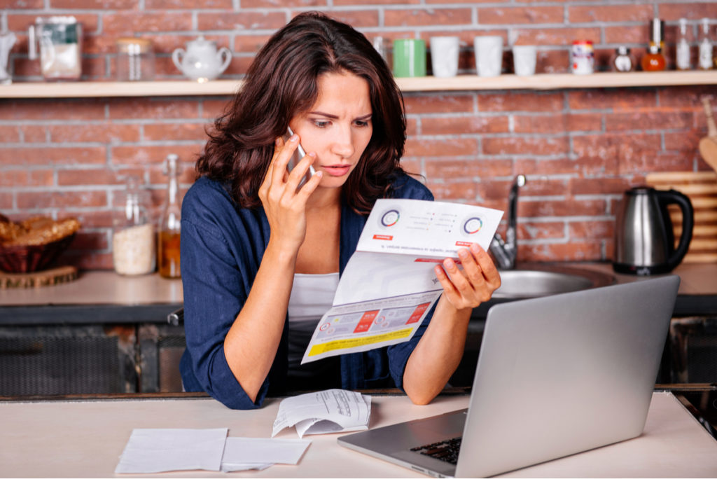 Woman looking at utility bill while on phone.