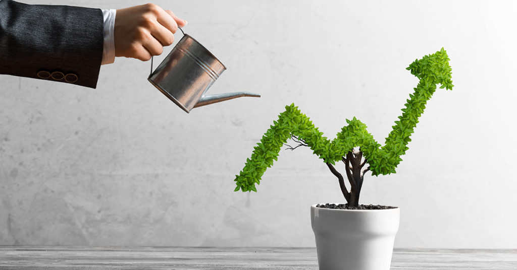 Image of business man watering plant shaped like an upward trend on a line graph